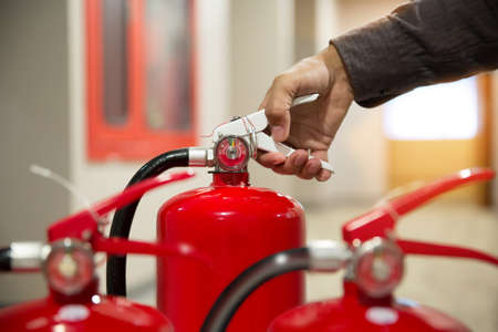Engineer checking Pressure gauge of Fire extinguisher for fire, emergence and safety Concept. Фото со стока