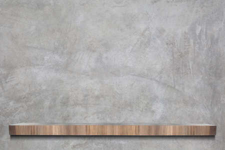 Muro de cemento u hormigón crudo con estantes de madera vacíos en estilo loft para el fondo.