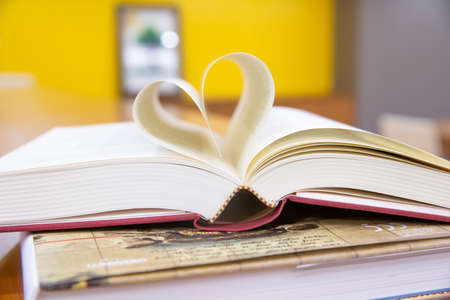 Close up book image in heart shape on the table at library room concept of lifestyle love to read. Stock Photo