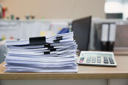 Pile of a lot papers documents on desk office stack up.