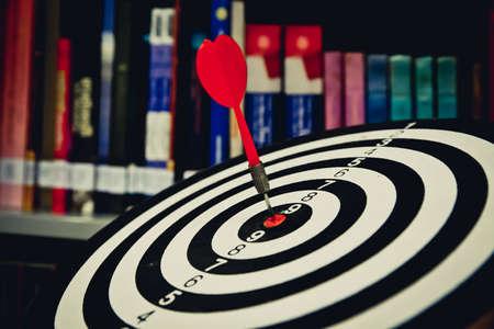 Red dart arrow hitting in the target center of dartboard on bullseye for Business focus concept. 版權商用圖片
