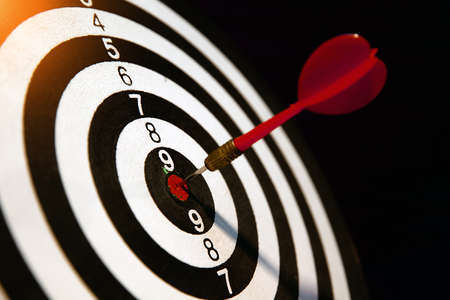 Close-up Dart board with arrow hitting in the target center, vintage style.
