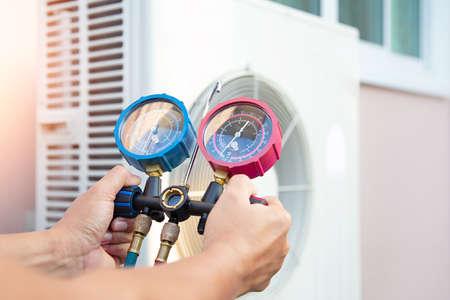 Handen van technicus gebruiken een meetinstrument om te controleren Vacuümpomp evacueert lucht voor airconditioner. Stockfoto