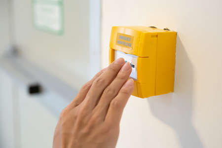 Close-up hand of firefighter to pull emergency switch in the building.