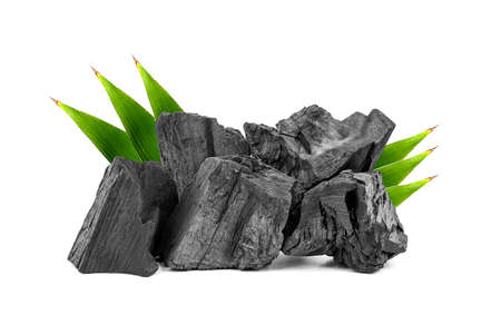 Natural wooden charcoal, Traditional or hard wood charcoal with bamboo leaves isolated on white background.