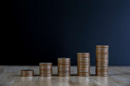 Many coins are stacked in a graph on the table for financial planning ideas and business growth
