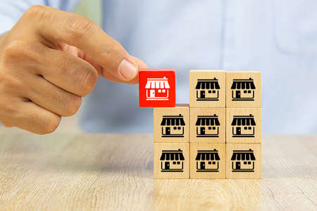 Franchise business,Businessman hand choose reg color wooden toy blog stacked with franchise marketing icons Store.