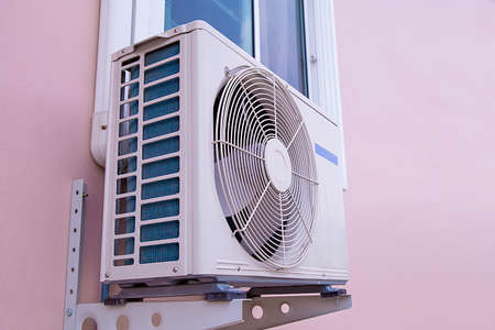 External split wall air conditioner compressor unit installed on the outside of the building.