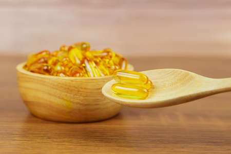 A pile of cod liver oil capsule in a wooden spoon. Dietary supplement for health-care concepts.