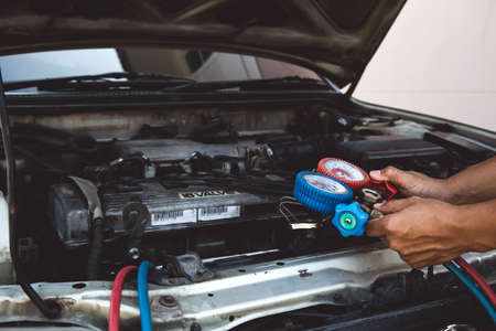 Auto mechanic using measuring equipment for filling car air conditioners checking. Concepts of car Repair service and car insurance.