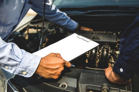 Auto mechanic using checklist for car engine systems after fixed. concepts of car insurance support and services.