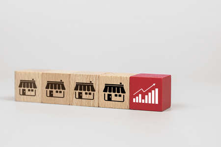 Cube wooden toy blogs with graph icon and franchise business store icon. for growth and branch expansion strategy of marketing financial. Archivio Fotografico