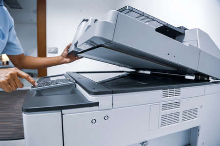 Man press the start button on the copier to using the photocopier for copy documents and scanning.