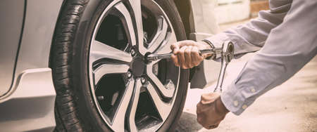 Close up hand of auto mechanic using wrench to changing a car tire. concepts of car insurance support, repair and services.