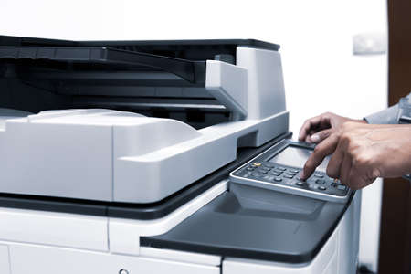 Businessman press the button using the photocopier or printer is office worker tool equipment for scanning document and copy paper. Standard-Bild