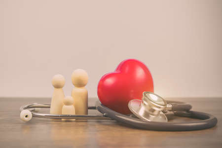 Family with stethoscope and a red heart. Concepts of a physical examination and health insurance.