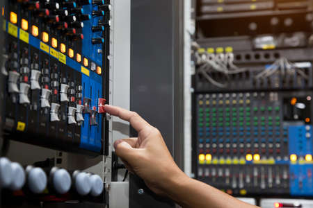 Close-up hand adjust the volume on sound mixer in studio workplace for live the media and sound recording equipment and sound system concept. Stok Fotoğraf