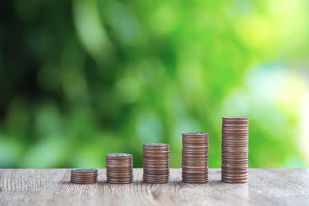 Many coins are stacked in a graph shape with green background for money saving ideas and financial planning insurance.