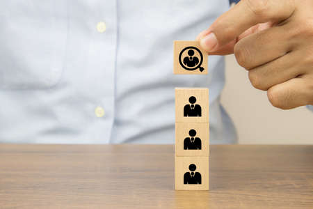 Close up hand choosing people in a magnifying glass icons on cube wooden toy blocks concepts human resources for business organizations and leadership.
