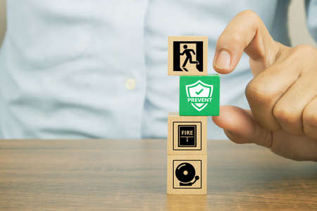 Close-up hand choose prevent symbol on cube wooden toy blocks stacked with fire exit icon for fire safety protection concepts.