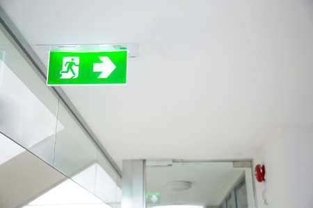 Close up green emergency fire exit sign or fire escape in the building Ideas for evacuation drills in the event of a fire.
