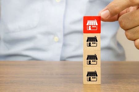Close-up hand choose cube wooden toy blocks place in line up with franchise business store icon. for small business growth and  branch expansion strategy of financial marketing planning.