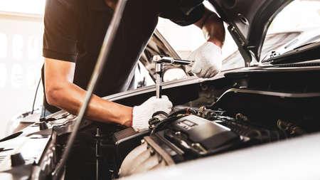 Close-up hand of auto mechanic using wrench to repair a car engine. concepts of car care fix repair service and insurance.