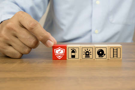 Close-up hand choose prevent icon on cube wooden toy blocks stacked with fire exit prevention icon for fire safety protection concepts.