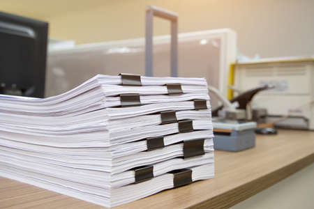 Pile of a lots paper and paperwork report or printout document on desk office stack up for work hard and information concepts.