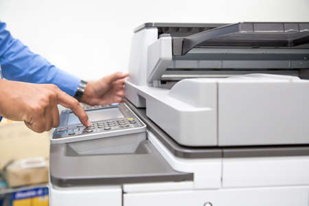 Closeup hand press button to using the photocopier or machine is office work tool printer equipment in copy room for scanning document and print a paper.