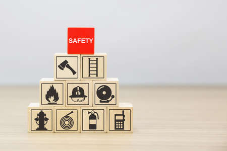 Wooded blocks stacked with fire and emergency icon for safety concept.