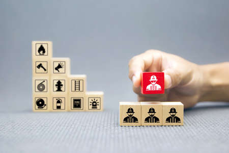 Hand choose wooden block with Firefighter icon for fire and safety Concept.