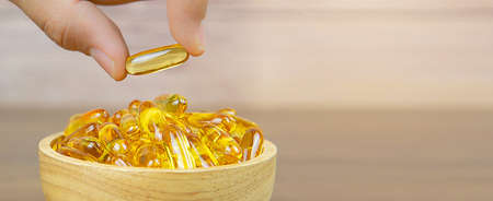 Hand picked cod liver oil capsule or fish oil in a wooden cup. Dietary supplement for health-care concepts.