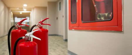 Red fire extinguishers tank at the exit door in the building concepts of emergency safety for fire prevention rescue and fire services concetps. Stock fotó