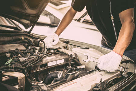 Close-up hands of auto mechanic are using the wrench to repair a car engine. Concepts of car care fix repair service and insurance. Foto de archivo