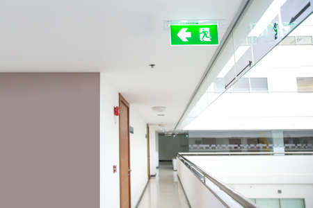 Green emergency fire exit sign or fire escape in the building ceiling emergency exit symbols in the event of a fire. Stock fotó - 155443240