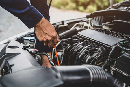 Auto mechanic are checking vehicle engine oil level to changing car engine oil concepts of maintenance repair service and car insurance.