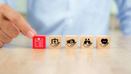 Close-up hand chooses cube wooden toy blocks with insurance icon for safety family insurance. Stock fotó