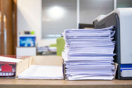 Pile of a lots reuse paper and paperwork report or printout document on desk office stack up for work hard and reduce recycle concepts.