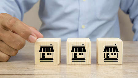 Close-up hand chooses cube wooden toy blocks stacked with franchise business store icon. For small business is growth and branch expansion strategy of financial marketing planning. Archivio Fotografico