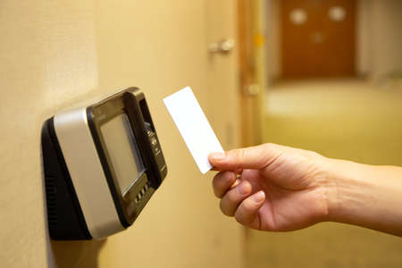 Office man using the ID card to scan at the access control system machine for check attendance and open the security door Imagens