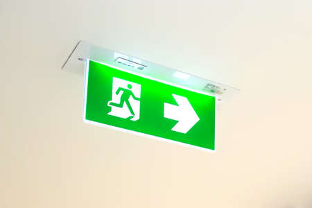 Green emergency fire exit sign or fire escape in the building ceiling emergency exit symbols in the event of a fire. Standard-Bild - 156025279