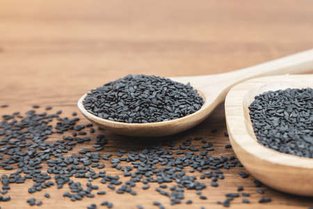 Black sesame seeds in a wooden spoon For healthy food and diet concepts. Standard-Bild - 156126033
