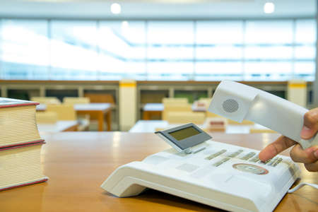 The hand picks up the phone and pressing the button on the office phone or old telephone. Standard-Bild - 156126035