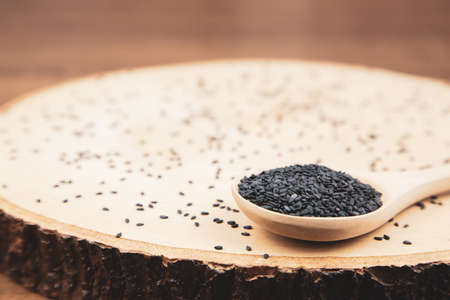Black sesame seeds in a wooden spoon For healthy food and diet concepts.
