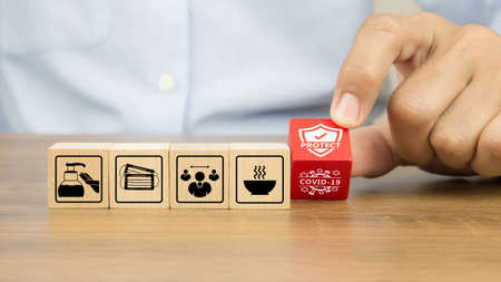 Close-up hand choosing covid-19 protection icon on wooden toy blocks concepts of protect and prevent of coronavirus.