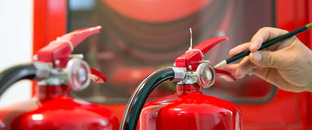 Fire fighter are checking pressure gauge of red fire extinguishers tank in the building concepts of fire prevention and safety of fire services training. Stock Photo