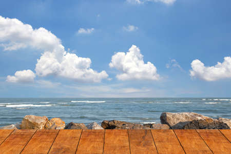 Wooden floor for the beach walkway with a rocky sea background blue sky and cloud. Standard-Bild - 156471531