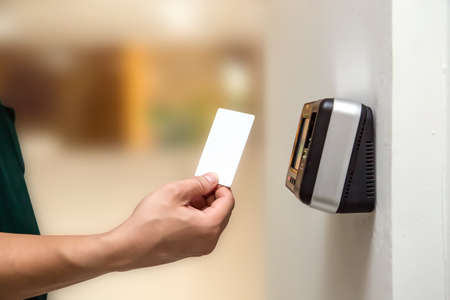 Office man using the ID card to scan at the access control system machine for check attendance and open the security door Standard-Bild - 156742975