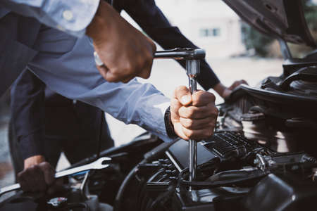 Close-up hands of auto mechanic are using the wrench to repair a car engine in auto car garage. Concepts of car care fixed repair and services. Standard-Bild - 156471569